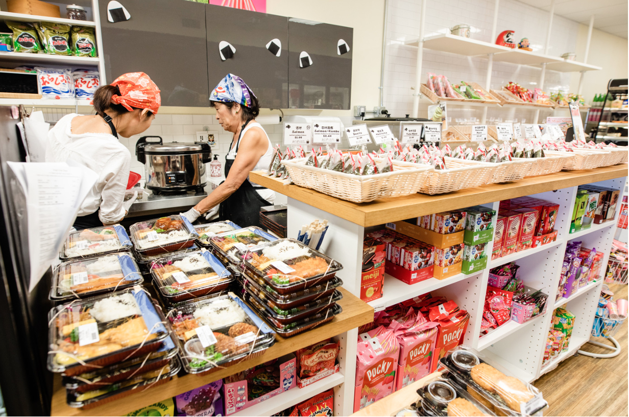 Two women at work in Asahi Imports, preparing goods that you can take and eat.